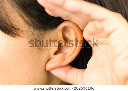 Extreme close-up of a young woman with hands cupped on ear and trying to listen