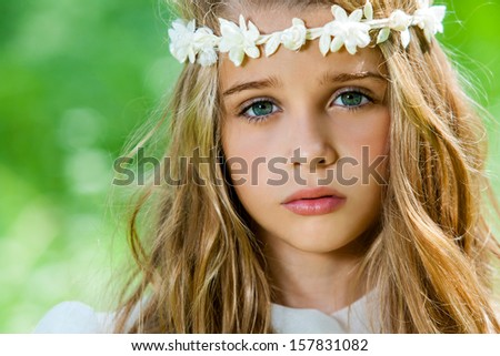 Extreme close up of cute girl with flower headband outdoors. - stock photo