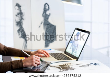Extreme close up of fashion student designing new collection with digital tablet and laptop. - stock photo