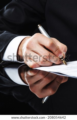Extreme close up of female business hand signing document. - stock photo