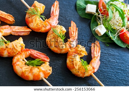 Extreme close up of grilled queen prawn brochettes spiced with natural herbs. - stock photo