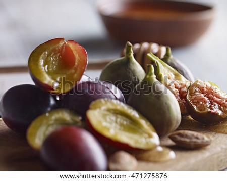 Extreme close up of plums and figs with honey. Selective focus.