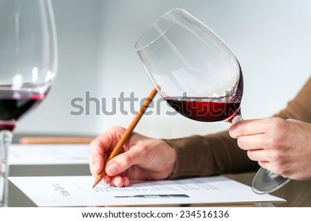 Extreme close up of sommelier evaluating red wine in wine glass at tasting.  - stock photo