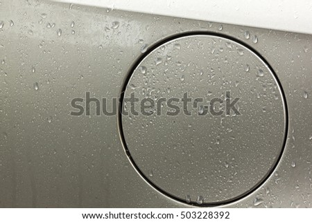 Extreme close up of wet vehicle body gasoline filler cap cover  with water droplets patterns and textures