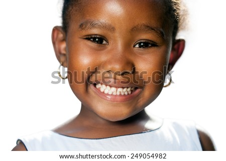 Extreme close up portrait of little African girl showing teeth.Isolated on white background. - stock photo