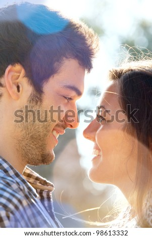 Extreme Close up portrait of romantic couple looking at each other outdoors. - stock photo