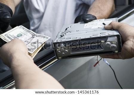 Extreme closeup exchange of car radio for cash - stock photo