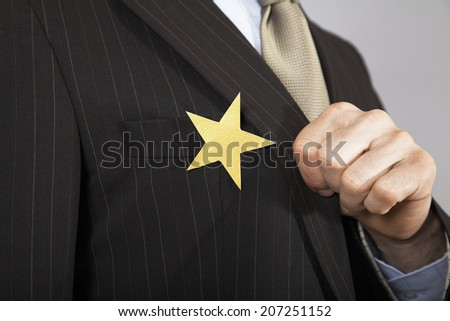 Extreme closeup of a businessman with gold star on suit - stock photo