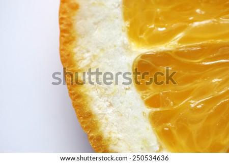 Extreme closeup of orange showing fruit flesh, pith and skin on white background - stock photo