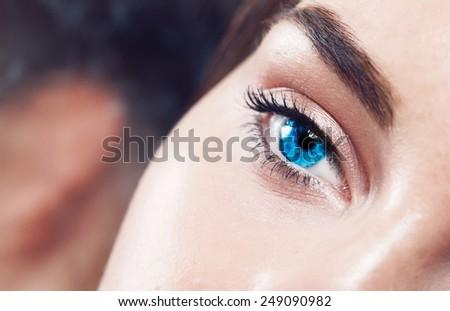 Extreme closeup shot of a beautiful woman  bright blue eye - stock photo