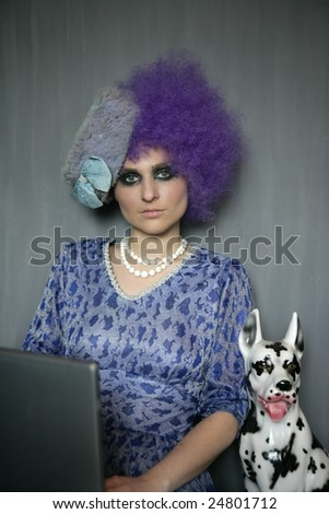 extreme contemporary fashion woman with computer and dalmatian dog, purple wig - stock photo
