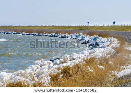 Extreme Ice Storm Hits Lake Shore. Thick ice coats the shore of a dutch lake - stock photo
