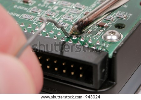 Extreme Macro Shot of a Harddrive being Soldered. - stock photo