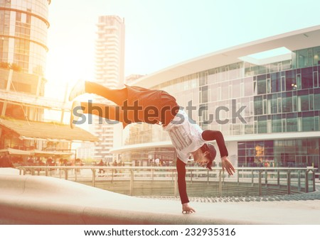 extreme parkour in business center. young boy performing some jumps from parkour discipline - stock photo