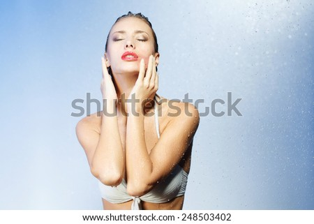 Extreme passion. Young beauty in sexual swimsuit standing under water shower and smearing her lipstick on blue background - stock photo