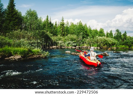 extreme rafting on the rapid river on an inflatable red kayak - stock photo