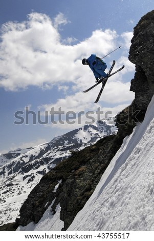 Extreme skier jumping with crossed skis against the blue sky.