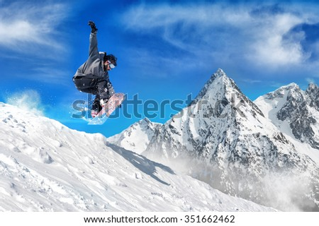 Extreme snowboarding man. Snowboarder jumping high in the air - stock photo