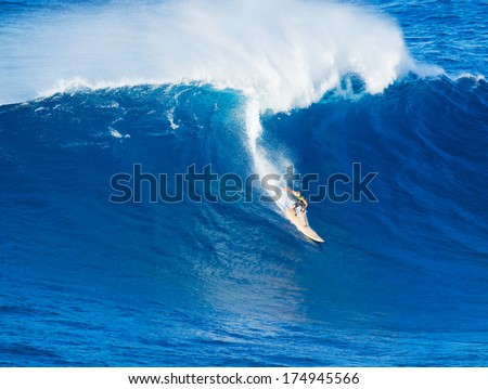 Extreme surfer riding giant wave  in Hawaii, Paddle in big wave surfing - stock photo