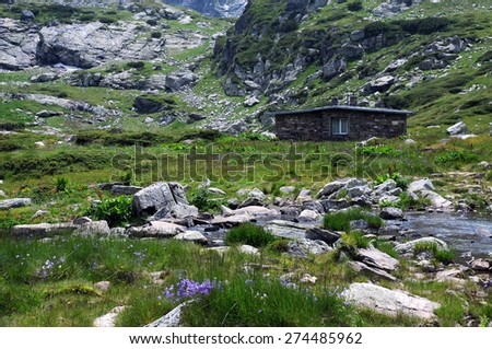 Extreme terrain, endemic flowers and lone house in the Rila mountains in Bulgaria - stock photo