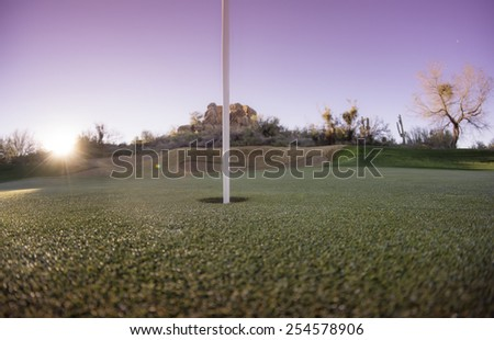Extreme wide angle viewpoint of putting green hole and flag with sun setting over mountains. Arizona,USA - stock photo