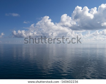 Extremely Calm Ocean Showing Partially Cloudy Blue Sky and Water - stock photo