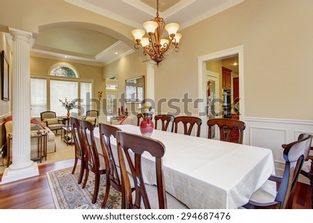 Extremely elegant dinning area with large table and many chairs.