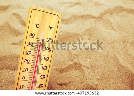 Extremely high temperatures, thermometer with celsius and farenheit scale on warm desert sand.