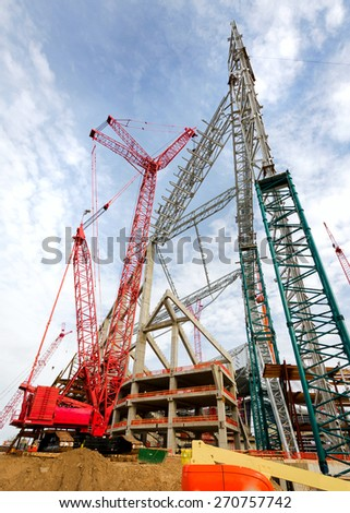 Extremely Large Red Crane Lifting Pieces of a Steel Structure - stock photo