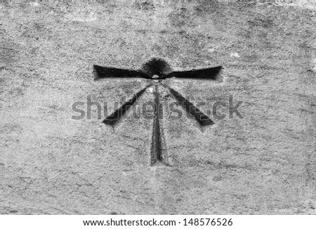 Extremely old symbol etched into a stone wall - stock photo