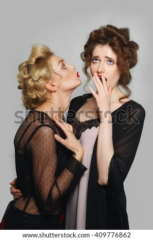 extremely surprised girl. girl whispering to her friend. blonde and brunette girls with natural make-up, blue eyes and red lips. - stock photo