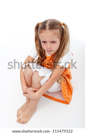 Extremely unhappy little girl sitting and crying - on white background - stock photo
