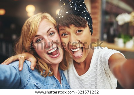 Exuberant happy multi ethnic girl friends enjoying a hearty laugh as they face the camera arm in arm inside a coffee shop, head and shoulders - stock photo
