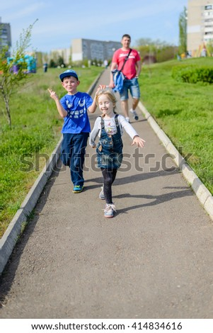 Exuberant young boy and girl clowning outdoors as they run along a path in an urban park followed by their father - stock photo