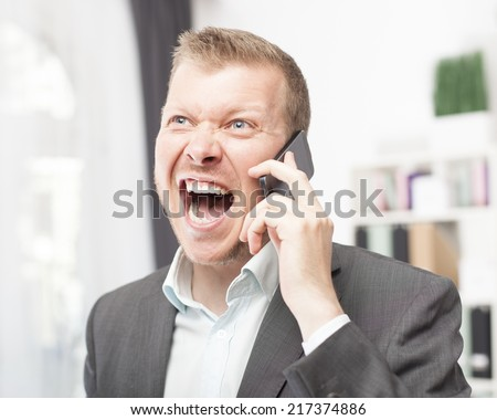 Exuberant young man in a suit jacket and open neck shirt shouting in reaction to a call on his mobile phone as he stands indoors at the office - stock photo