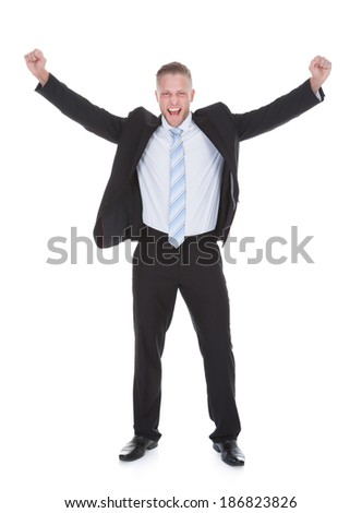 Exultant stylish young businessman in a suit standing cheering and raising his fists in the air as he celebrates a success  full length isolated on white - stock photo