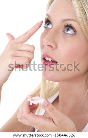 Eye-care - young woman putting contact lenses  - stock photo