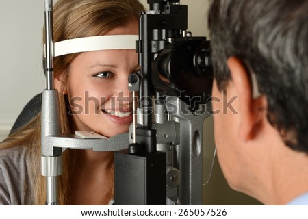 Eye Doctor druring a test with young patient in his office - stock photo