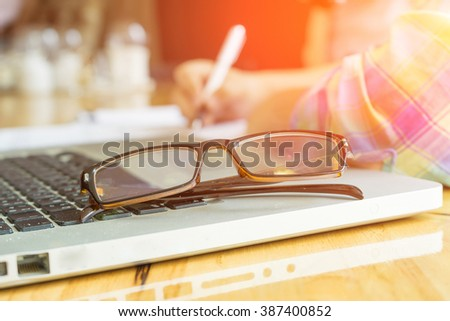 Eye Glasses on Businessman Wooden Table with Other Stuffs - Keyboard, Notebook, Pen and Phone.Office workplace with laptop , smart phone ,businessman work in Office desk,selective focus ,vintage tone - stock photo