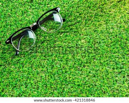 Eye glasses on grass field - stock photo