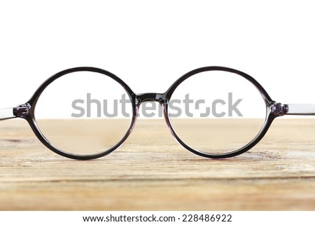 Eye glasses on wooden table on white background - stock photo