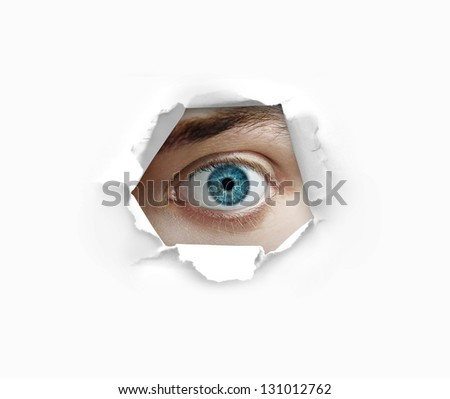 Eye looking through a hole in paper - stock photo