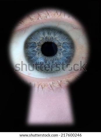 Eye looking through keyhole - stock photo