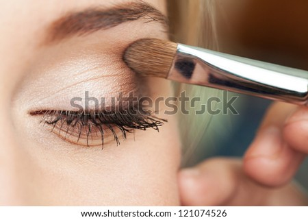 Eye makeup woman applying eyeshadow powder - stock photo