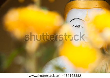 Eye of buddha Myanmar with yellow flower - stock photo