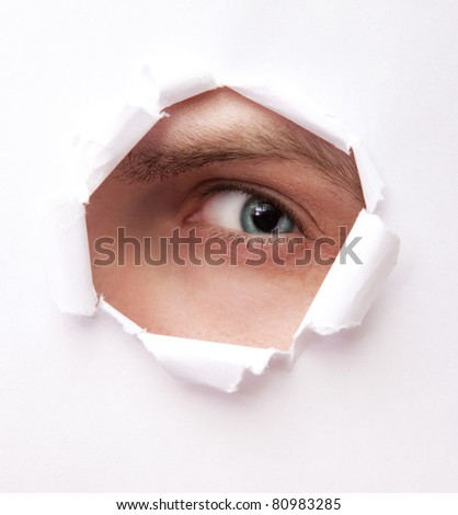 Eye of young man looking from paper hole - stock photo