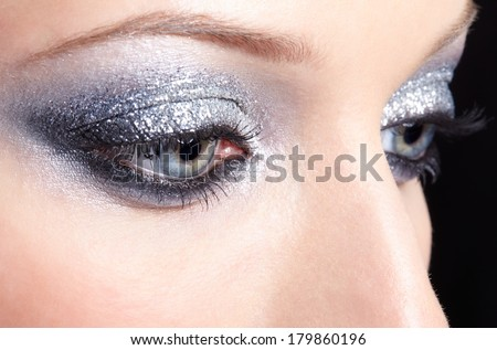 Eye of young woman with vogue shining sparkle makeup - stock photo