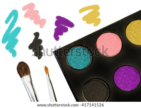 Eye shadows colors palette in trendy purple gold gray and turquoise colors isolated on white. Beautiful trendy eye colors with shimmer texture. Eye shadows and brushes collage.