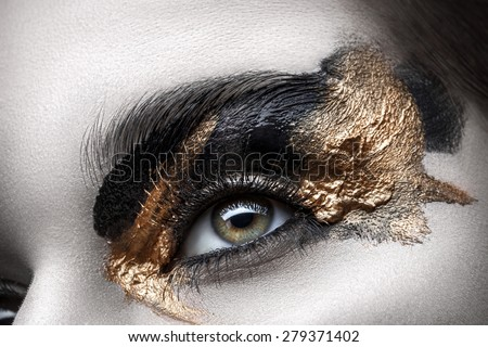 Eye with long eyelashes and black and gold makeup closeup