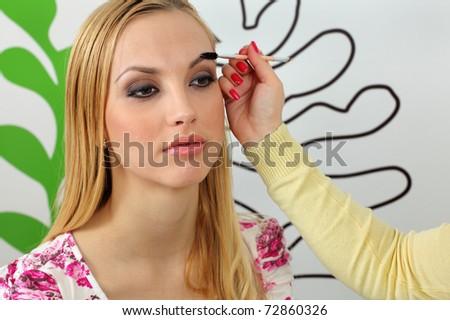 Eyebrow shaping in professional studio - stock photo